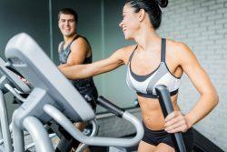 female on elliptical machine with a gym go-er beside her